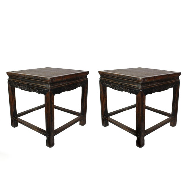 Featured are a pair of late 19th century Qing Dynasty Chinese square side or end tables, hand carved with openwork dragon-...