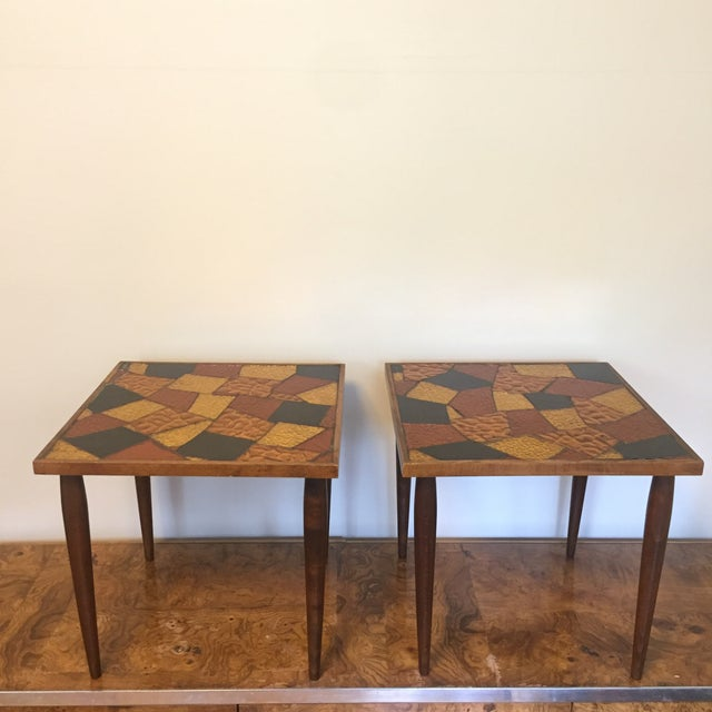 A pair of gorgeous wooden side tables with tapered legs and vibrant mosaic foil glass tops designed by Jon Matin. Both...