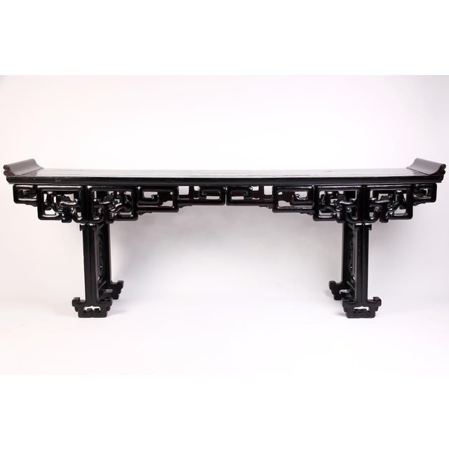 This handsome and lengthy table features a rich, dark patina throughout. Rounded everted flanges move fluidly down into...