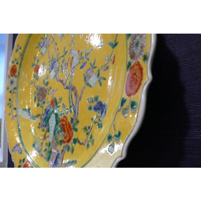 Oversized charger featuring asian-inspired chinoiserie pattern, with vibrant hues of yellow, rust, blues & greens....