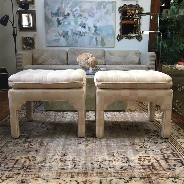 A pristine pair of matching tufted ottomans with Moroccan style detail. The original upholstery is an ivory and blush...