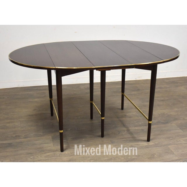 """A mid century mahogany dining table with four 11"""" leaves designed by Paul McCobb for H Sacks & Sons """"Connoisseur..."""