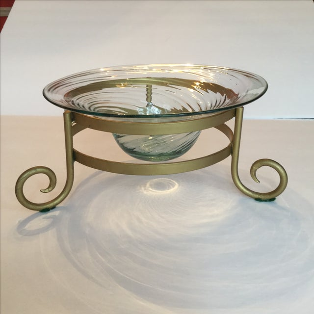 Bowl of swirling faintly green glass supported by a gold tone metal tripod. Perfect for holiday decorations or fruit but...