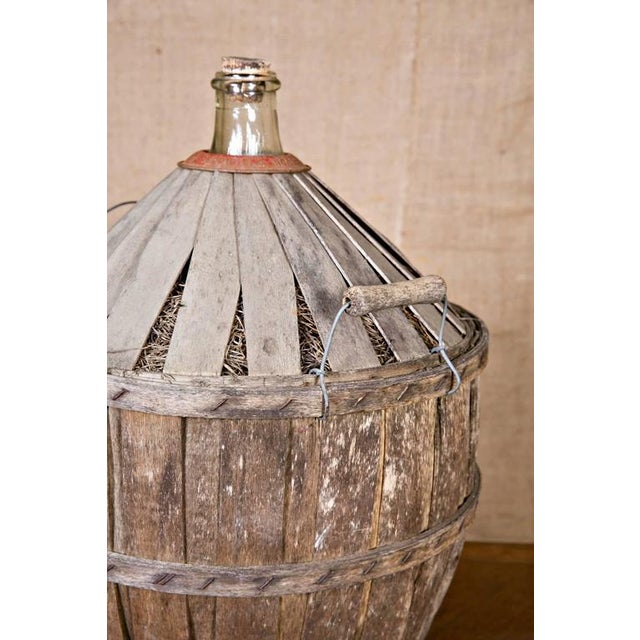 Charming antique French demijohn or bonbonne with handles, encased in original wooden slat protection. Red metal collar...