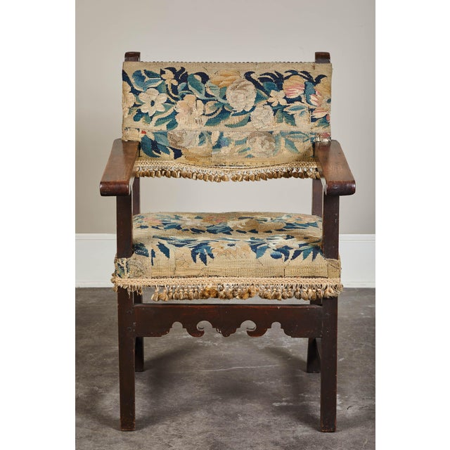A 19th century Spanish walnut armchair. Beautiful patina. Upholstered in a tapestry with a tassel trim that circles around...