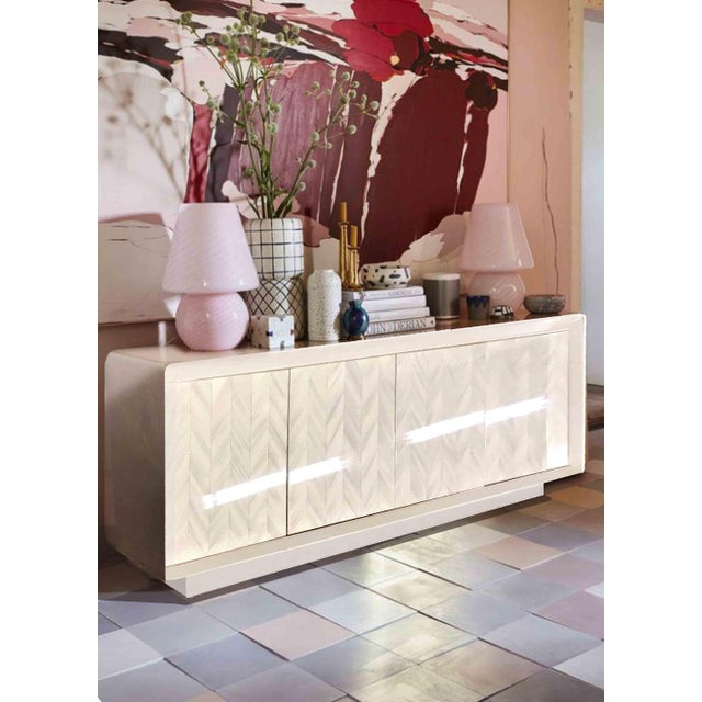 We love this vintage cream lacquer and herringbone pattern credenza. With curvy chamfered corners and sleek lines, this...
