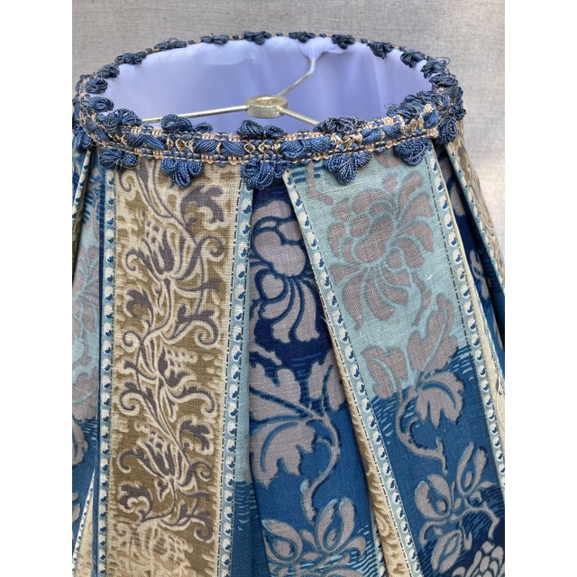 A large hand pleated lampshade made from a 19th century blue and grey printed cotton, embellished with coordinating...