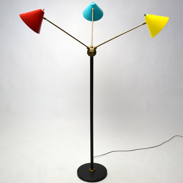 A wonderful example of Italian Mid-Century lighting, this three-arm floor lamp has conical-shades in red, yellow and blue...