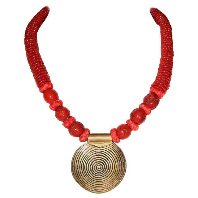 Circa 1970s to 1980s coral bead necklace with a large brass disk pendant. The necklace is hand-tied together with coral-...