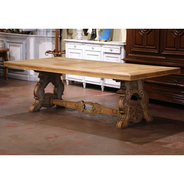This elegant and large antique dining room table was crafted in France, circa 1920. Standing on a trestle base with two...
