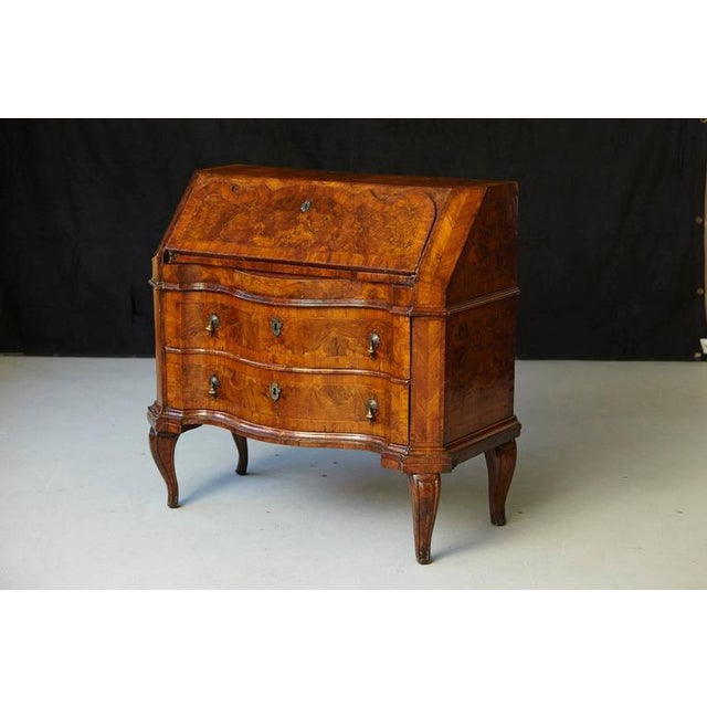 Italian burled walnut slant front desk. The slant drop front with key cartouche and shaped border, opens to reveal...