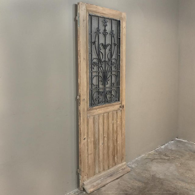 19th Century Entry Door with Wrought Iron features amazing detail in the hand-forged, solid iron window insert to present...