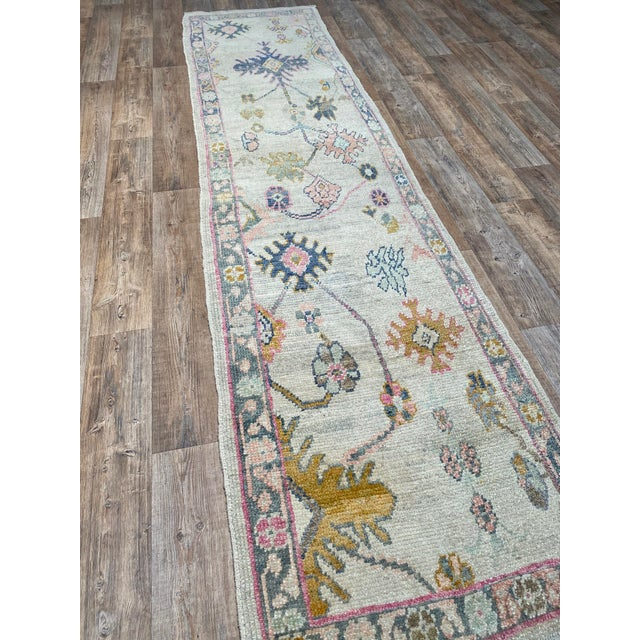 A colorful Turkish Oushak runner rug. This runner offers a neutral palette with pops of soft pastel colors.