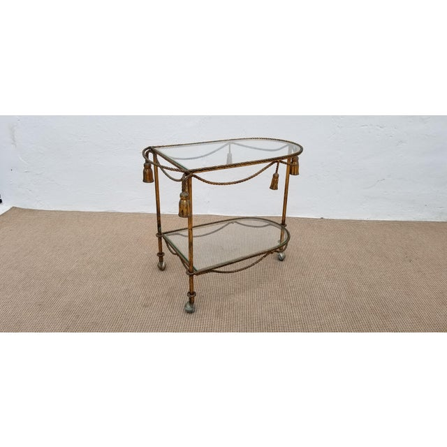 Italian Hollywood Regency gilt metal rope and tassel two tier bar cart. Nice vintage condition with some patina shown in...