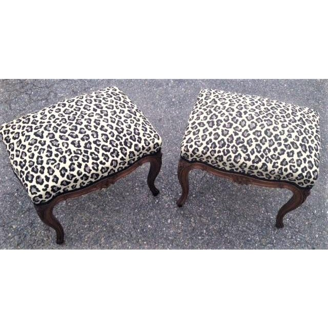 Nice pair of carved walnut French Louis XVth style foot stools with paw print upholstery. Stools have cabriole legs joined...