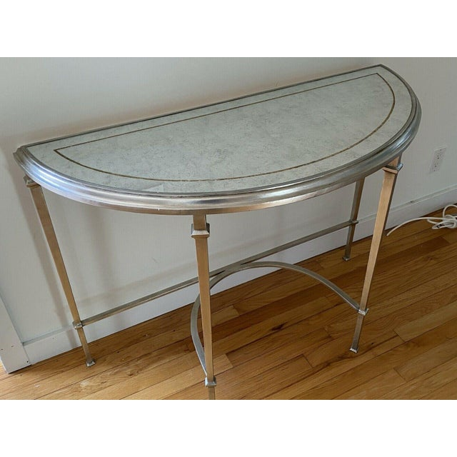 A sublimely refined demilune console table in the Louis XVI style with an inset mirrored top and wrought iron base...