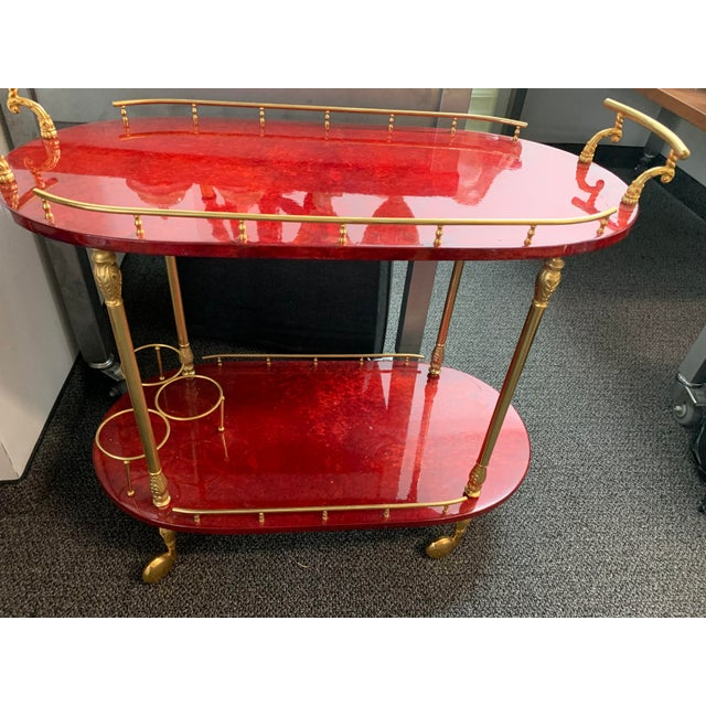 Created in a two tiered lacquered goatskin this is a cocktail bar table on wheels with side rails and three bottle...