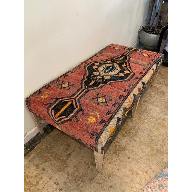 We've repurposed an aged coffee table and upholstered it with a vintage Persian rug in hues of terracotta, coral, navy,...