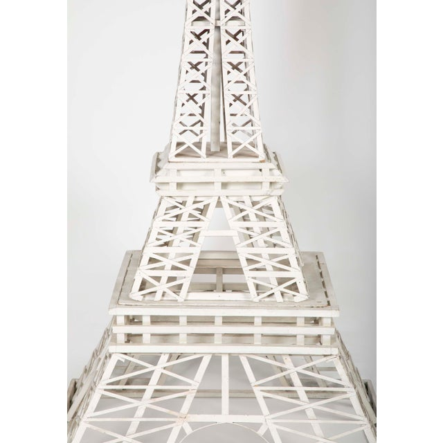 A handmade 123 to 1 scale model of the Eiffel Tower consisting of 783 pieces of wood. Together with the original newspaper...