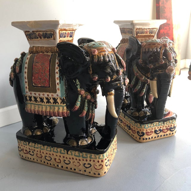 The colors on this pair of vintage elephant plant stands/stools are rich and vibrant. They would also be great as a...