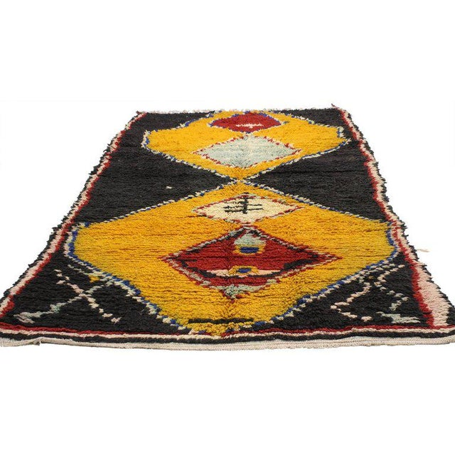 A vintage Berber Moroccan rug with tribal style. Jet black coffee (espresso color) sets the stage for diamonds colored in...