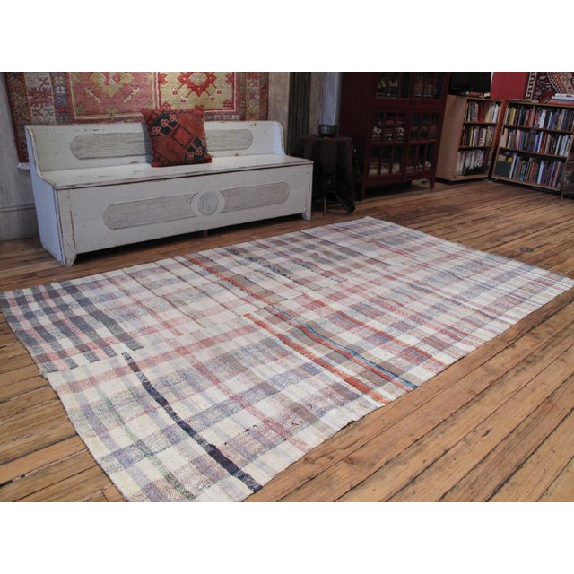 A simple, old tribal floor cover, made for everyday use, with a soft, pastel color palette.