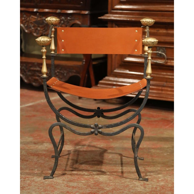 This elegant, antique Campaign armchair was created in Italy, circa 1880. The frame of the chair is formed from forged...