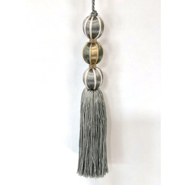 A festive, ornamental French blue & soft gold beaded key tassel. The tassel is connected by a twisted cord that loops over...