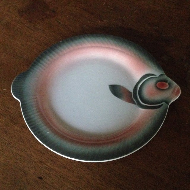 A vintage, French made, porcelain plate in the shape of a fish. The vintage piece features gorgeous tones of green, peach...