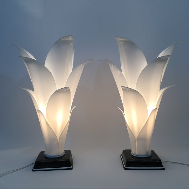 A beuatiful pair of table lamps with molded white lucite petals and a black lucite base by Rougier, Really great pair in...