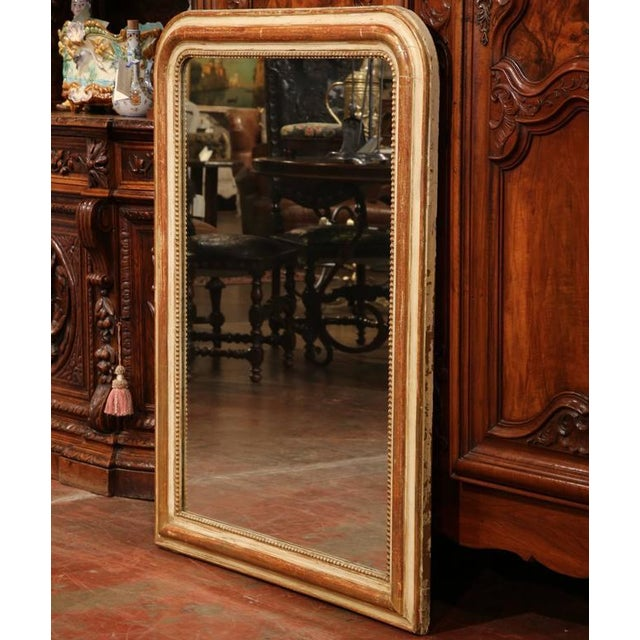 This large, antique Louis Philippe mirror was crafted in France circa 1870. The rectangular mirror has rounded corners and...