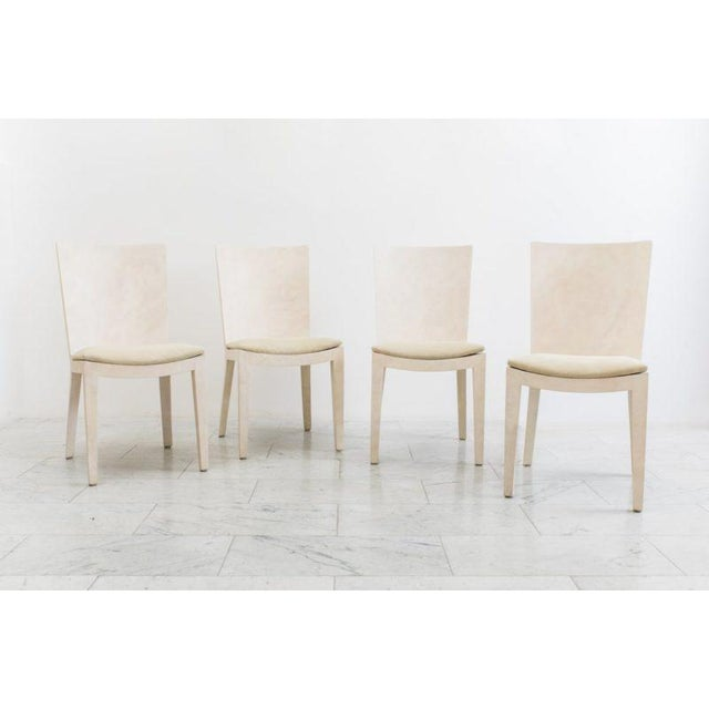 A set of four matte ivory parchment JMF chairs by Karl Springer. Excellent condition.