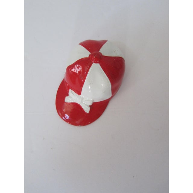 "A circa 1940's red and white jockey cap bottle opener. Measures 3.5""W x 2""H. Concealed bottle opener in base Some chips in..."