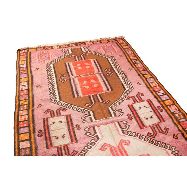 This traditional kilim is pretty in pink. An array of pink, orange, yellow, gold, blue and brown come together to create...
