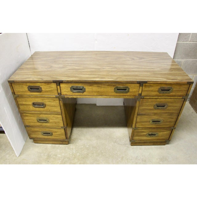 Midcentury Campaign-style partner's desk by Bernhardt. Features seven drawers, including a file drawer with recessed brass...
