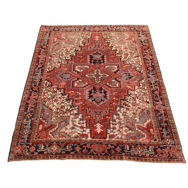 This is a hand knotted wool Persian Hariz rug with a geometric medallion design in hues of red and cream.