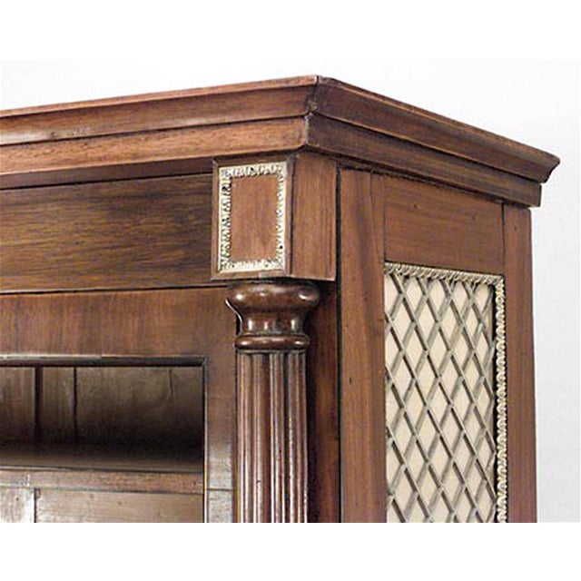 English Regency mahogany bookcase with reeded columnar angles flanking glazed doors over green silk lined brass grilled...