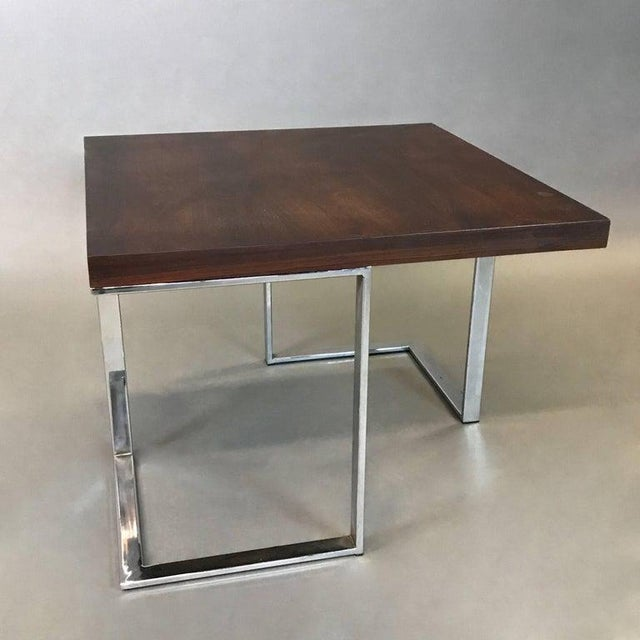 Striking, modernist coffee or side table features a rosewood top with architectural chrome bases is very much in the style...