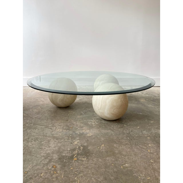 Fabulous marble and glass top coffee table. 3 solid marble globes support a round beveled glass table. Each marble is a...