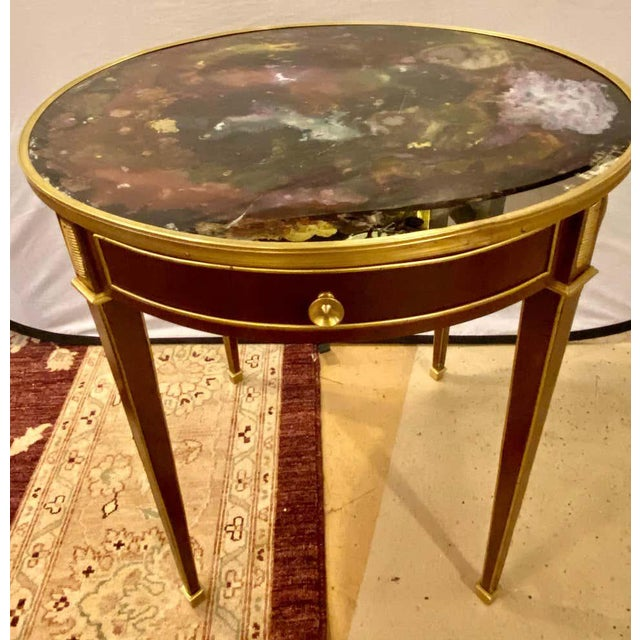End, center or sofa table bronze mounted single drawer multi-color glass top in the manner of Masion Jansen. This finely...