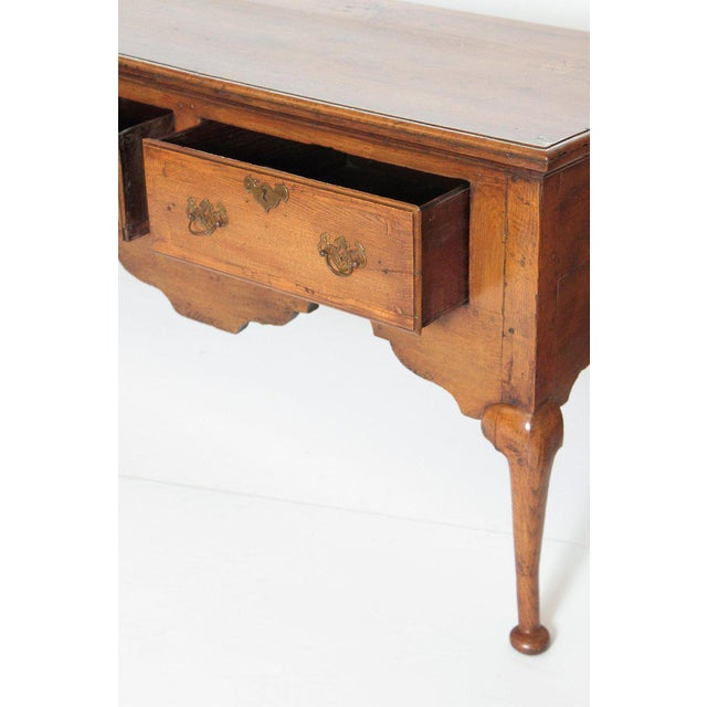 This English Queen Anne style oak dresser base features a rectangular top with a cornice edge over three cross- banded...