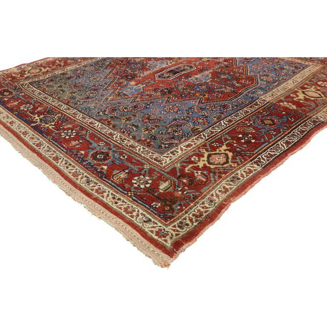 This hand-knotted wool antique Persian malayer rug features a large-scale red serrated-edged hexagonal medallion floating...