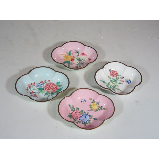 The scalloped bowls are applied enamel over brass. They are hand painted with floral decorations. Each bowl is marked...