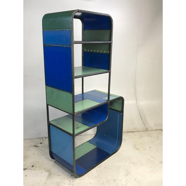 Curvaceous bookcase or shelving unit with strong blue and green colorations. Hand fabricated from reclaimed steel by...