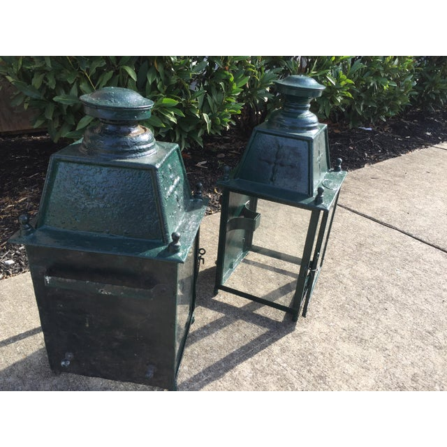 Wonderful pair of antique french exterior lanterns, c. 1900. They are painted green and mount to an exterior wall. In...