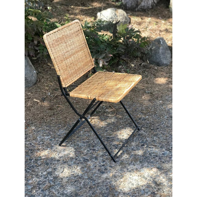 Offering a vintage rattan and wrought iron folding chair. This sweet little chair folds nicely and is in very good vintage...