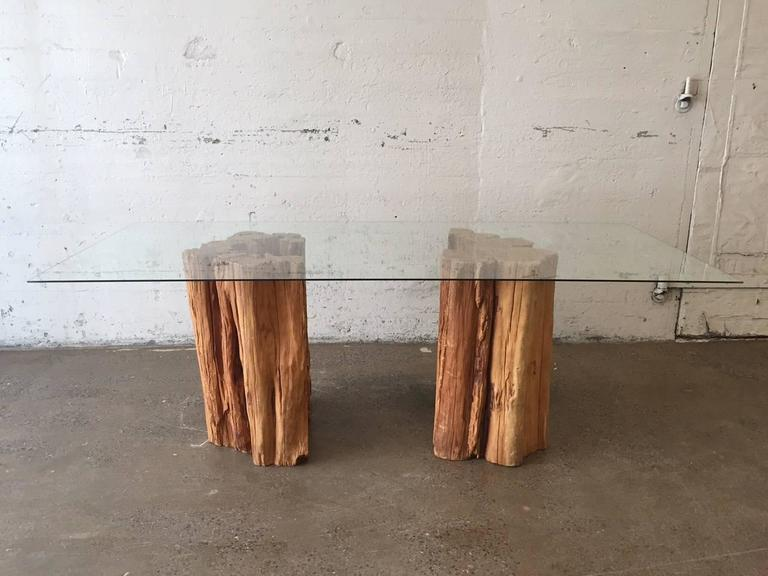 Halved Ipe Wood Trunk Pedestal Dining Table With A Glass Top. The Trunks  Have Natural