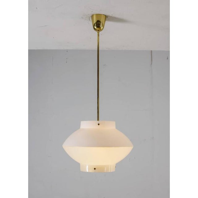 A white plexiglass model 61-380 pendant by Yki Nummi for Orno, Finland. The lamp has a brass ceiling mount and stem and a...