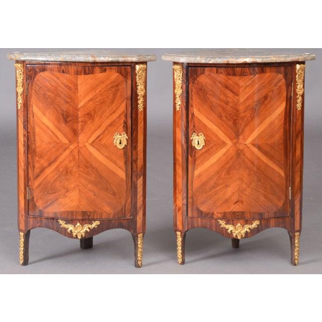 A lovely pair of Louis XVI Ormolu-mounted kingwood and tulipwood parquetry encoignures. Each with a bow-fronted marble top...