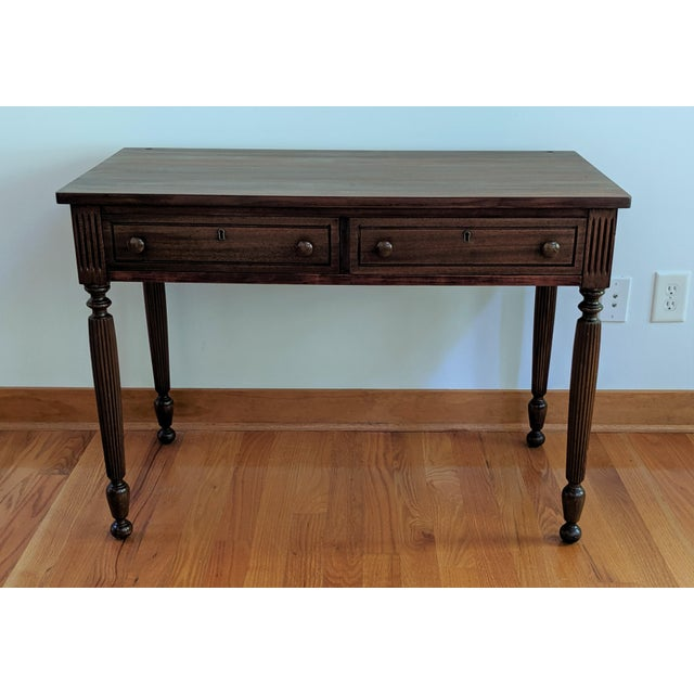 A finely crafted antique mahogany vanity with tri-fold mirror. This turn of the century piece is rich in details and...